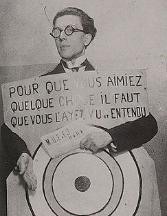 André Breton in 1920, at a Dada festival in Paris wearing a sign designed by Francis Picabia