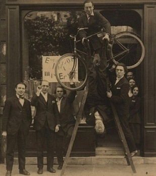 Opening of the Ernst exhibition at the gallery Au Sans Pareil, Paris (1921). From left: René Hilsum, Benjamin Péret, Serge Charchoune, Philippe Soupault on top of the ladder, Jacques Rigaut (upside down), and André Breton