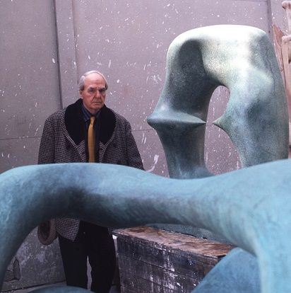 Henry Moore standing next to his sculpture Working Model for <i>Oval with Points</i> (1975)