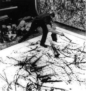 A photograph of Jackson Pollock making one of his drip paintings, taken by Hans Namuth in 1950.