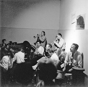 Jerry Burchard's photograph <i>Studio 13 Jazz Band playing in the social hall at the California School of Fine Arts, 1957</i> shows, from left to right, Joan Brown observing, David Park on the piano, Wally Hedrick on banjo, and trumpet player Elmer Bischoff.