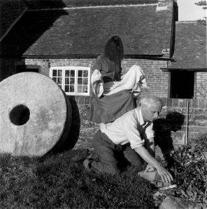 Miller's photograph <i>Dorothea Tanning and Max Ernst, Farley Farm</i> (1953). For her final photo essay published in <i>Vogue</i>, Miller put her art world friends to work around her farm. Surrealist artist Max Ernst, here, planting petunias, introduced Miller to her second husband, Roland Penrose, in 1937