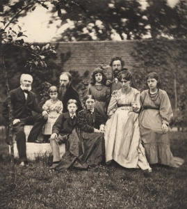 The Morris and Burne-Jones families at The Grange, the West London home of Burne-Jones. Morris stands to the right behind his wife and two daughters, while Burne-Jones sits at center-left with his wife, children, and father to the far left. The photograph by Frederick Hollyer (1874) is held at the National Portrait Gallery.