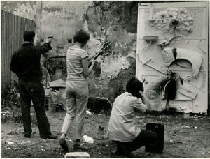 Jean Tinguely (far left) Niki de Saint Phalle, and unidentified man, shooting paint at a nearly finished work (1961). Photo by Shunk-Kender