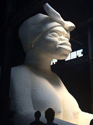 A side view of the monumental work <i>A Subtlety, or the Marvelous Sugar Baby an Homage to the unpaid and overworked Artisans who have refined our Sweet tastes from the cane fields to the Kitchens of the New World on the Occasion of the demolition of the Domino Sugar Refining Plant</i> (2014)